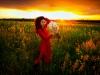 sesja-kobieca-plener-zachod-slonca-kobieta-w-czerwonej-sukience-z-bukietem-rumianku-okolice-Tarnowa